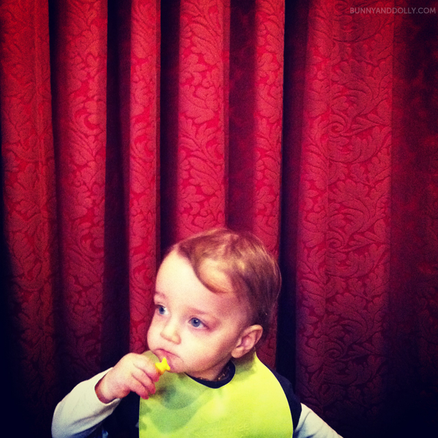 toddler eating goldfish crackers in front of red curtain