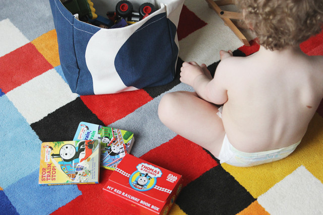 Toddler playing on The Land of Nod rug in a boys' shared bedroom