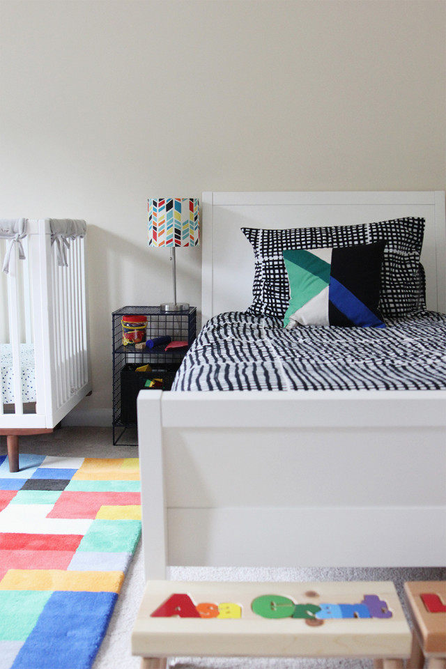 A twin bed and a crib in a boys' shared bedroom.