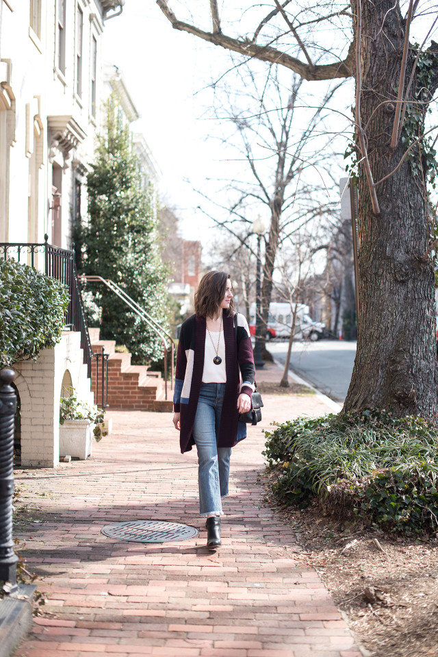 An early spring outfit: high-rise, frayed-hem cropped flare jeans with a sweater cardigan and wedge boots
