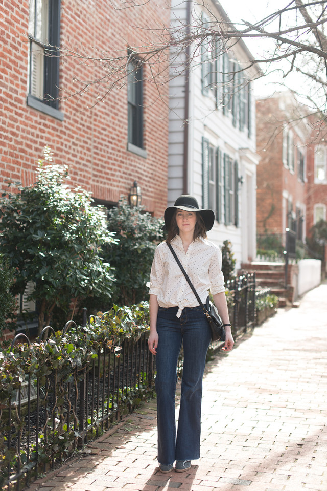 A classic black and white polka dot shirt tied at the waist with flare jeans