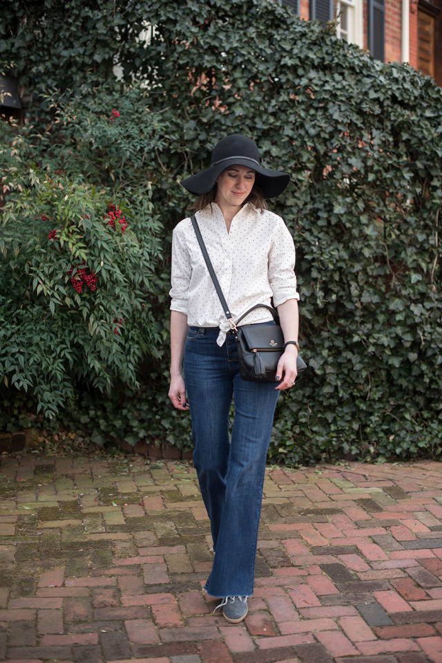 A simple black and white polka dot shirt with flare jeans and a floppy black hat