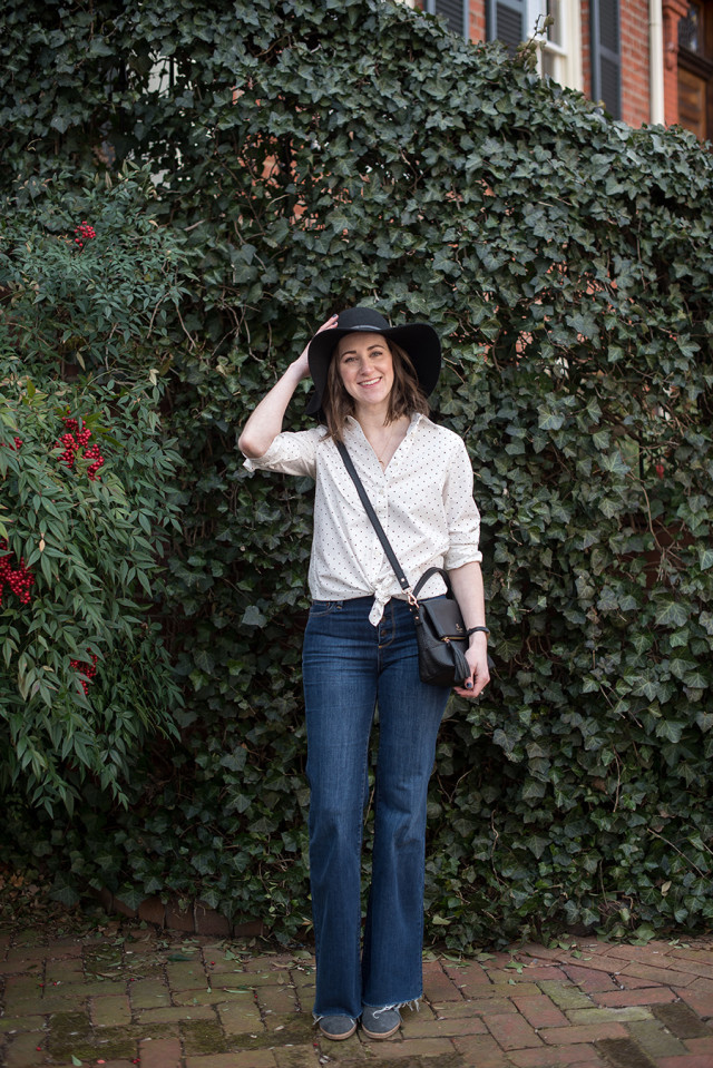 A polka dot shirt tied at the waist, flare jeans, and a black floppy hat for spring