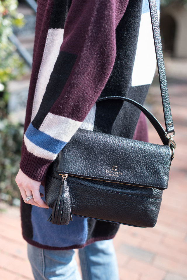 Kate Spade purse with tassel and a color block cardigan sweater with a pair of cropped frayed-hem cropped flare jeans