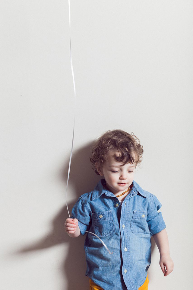 toddler holding balloon string