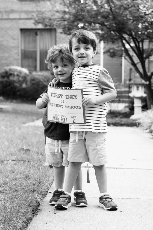 Brothers holding a first day of nursery school sign together