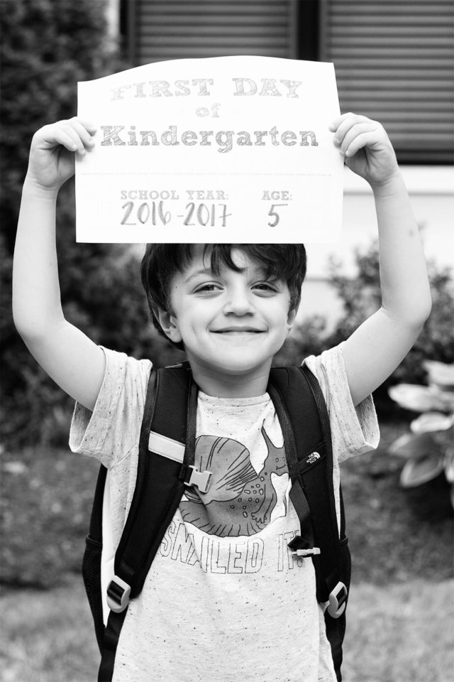 Holding a First Day of Kindergarten sign!