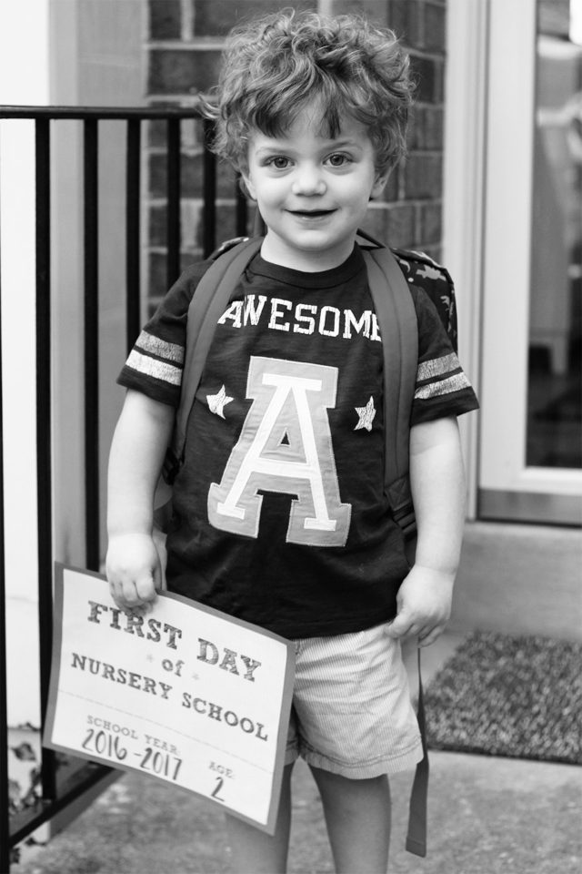 Toddler holding a first day of nursery school sign