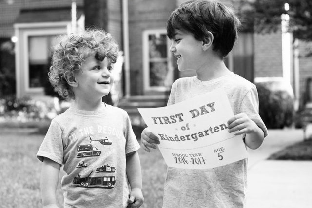 Brothers on the first day of school holding a kindergarten sign