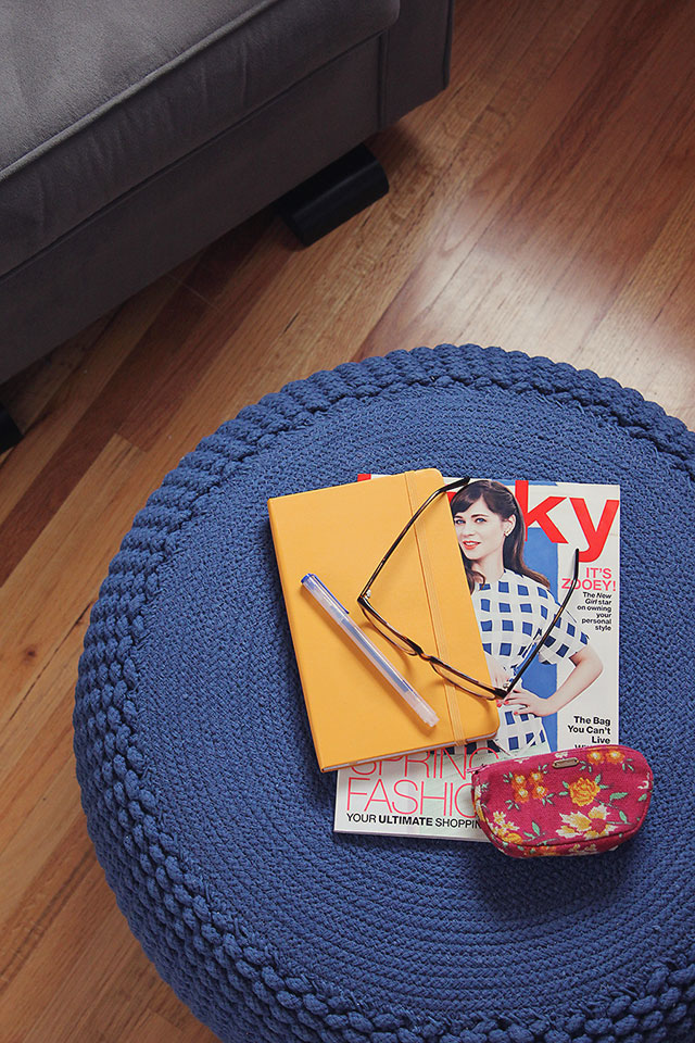 notebook and magazine stack on blue knitted pouf